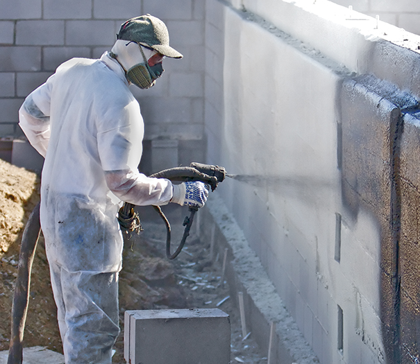 Contractor spraying coating with a Graco Reactor Plural-Component Sprayer